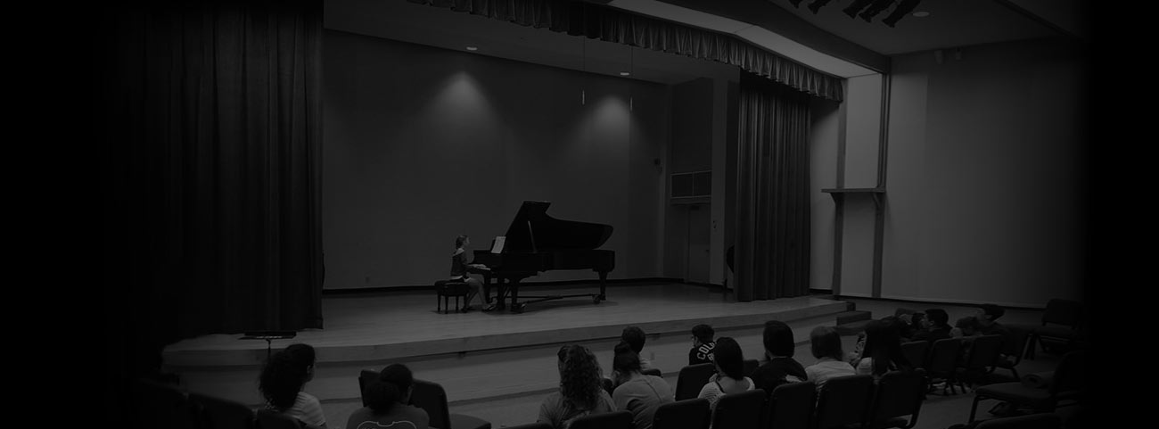 Young student performing piano recital on stage